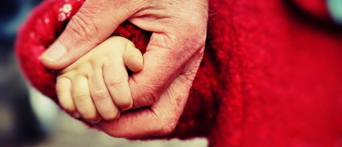 An older person holds a child's hand